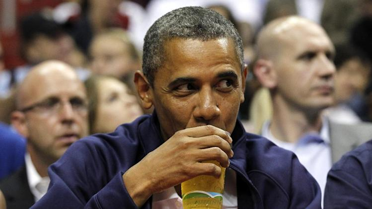FILE - In this July 16, 2012 file photo, President Barack Obama sips his beer as he watches Team USA and Brazil during the first half of an Olympic men's exhibition basketball game, in Washington. Obama and his team frequently talk about the president's fondness for beer, and Obama has been photographed many times downing a beer, including an appearance at the Iowa State Fair last month. Being identified as a beer drinker is an easy way for Obama to connect with votes and serves as a not-so-subtle reminder that his Republican rival Mitt Romney, a Mormon, doesn't drink. (AP Photo/Alex Brandon, File)