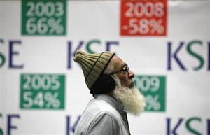A trader monitors an electronic board (unseen) displaying index during a trading session at the Karachi Stock Exchange