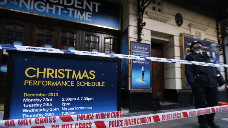 A police officer stands on duty next to a notice board is wrapped in police tape outside the Apollo theatre on the morning after part of it's ceiling collapsed on spectators as they watched a performance, in central London