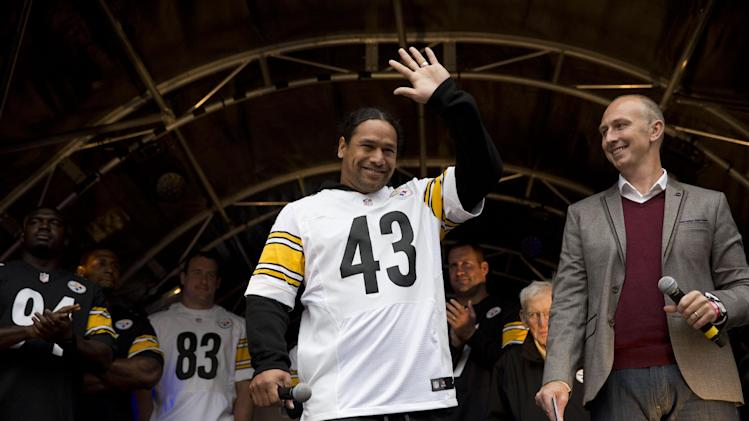 Pittsburgh Steelers strong safety Troy Polamalu, 43, waves as he is introduced on stage during an NFL fan rally event in Regent Street, London, Saturday, Sept. 28, 2013.  The Minnesota Vikings are to play the Pittsburgh Steelers at Wembley stadium in London on Sunday, Sept. 29 in a regular season NFL game