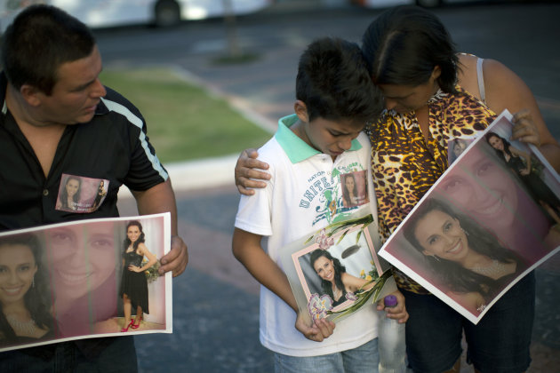 Relatives hold photographs of Pamella Lopes, who died in a nightclub fire, as they stand a public square near the nightclub in Santa Maria, Brazil, Monday, Jan. 28, 2013. A fast-moving fire roared thr