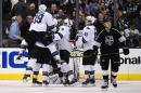 Members of the San Jose Sharks, left, celebrate a game-winning goal by center Patrick Marleau as Los Angeles Kings center Tyler Toffoli, right, looks on during the overtime period in Game 3 of an NHL hockey first-round playoff series, Tuesday, April 22, 2014, in Los Angeles. The Sharks won 4-3. (AP Photo/Mark J. Terrill)