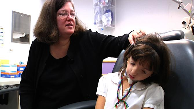 In this Feb. 6, 2012 image made from video, Dr. Nancy Young, of the pediatric otolaryngology division at Children's Memorial Hospital, examines 9-year-old Clara Beatty's hearing aids during a visit to the hospital's offices in Glenview, Ill. Clara, who was born with a genetic mutation called Treacher Collins syndrome, uses special hearing aids that attach with magnets placed under her skin because she has very narrow ear canals and only remnants of outer ears. (AP Photo/Martha Irvine)