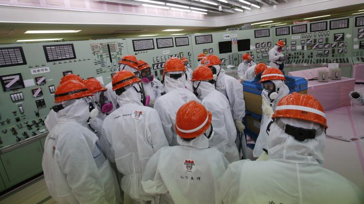 Members of media and TEPCO employees wearing protective suits and masks visit central control room for No. 1 and No. 2 reactors at tsunami-crippled TEPCO's Fukushima Daiichi nuclear power plant