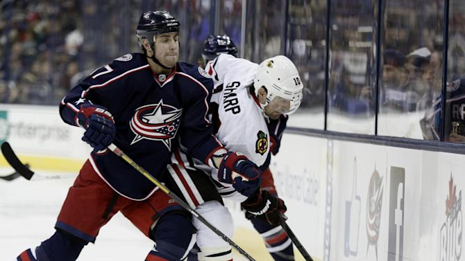Columbus Blue Jackets' Brandon Dubinsky, left, and Chicago Blackhawks' Patrick Sharp work for the puck in the first period of an NHL hockey game in Columbus, Ohio, Saturday, Jan. 26, 2013. (AP Photo/Paul Vernon)
