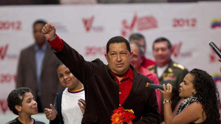 Venezuela's President Hugo Chavez gestures as rap singer Rodbexas, right, sings during an event at Teresa Carreno theater in Caracas, Venezuela, Thursday March 29, 2012.  Chavez returned home after a five-day round of radiation therapy in Cuba, where he has been undergoing cancer treatment. (AP Photo/Ariana Cubillos)