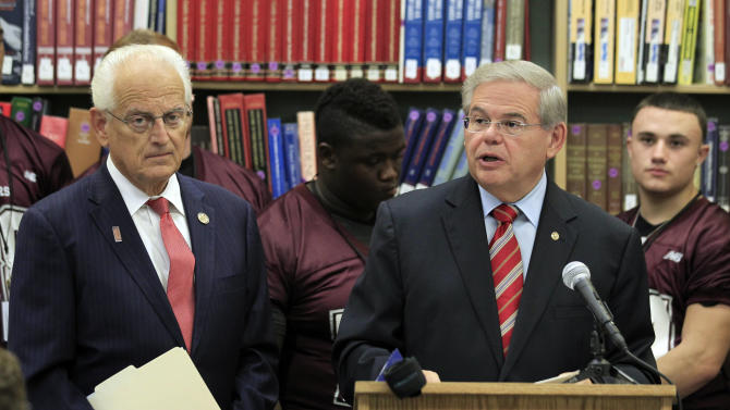 U.S. Sen. Robert Menendez, right, stand next to U.S. Rep. Bill Pascrell, left, and football players from Nutley High School to announce that the Centers for Disease Control and Prevention will be developing national guidelines for managing sports-related concussions for student athletes, Tuesday, Sept. 27, 2011, in Nutley, N.J. According to the politicians, the CDC has agreed to adopt a key element of stalled legislation they sponsored which would have made such protocols mandatory. The lawmakers say the CDC protocols will be ready by 2014.  (AP Photo/Julio Cortez)