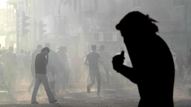 Bahraini anti-government protesters react to tear gas during clashes with riot police in Sanabis, Bahrain, on Friday, Oct. 5, 2012. Riot police used water cannons and tear gas on Friday to disperse hundreds of anti-government protesters trying to reach a heavily guarded site that was once the hub of their uprising. (AP Photo/Hasan Jamali)