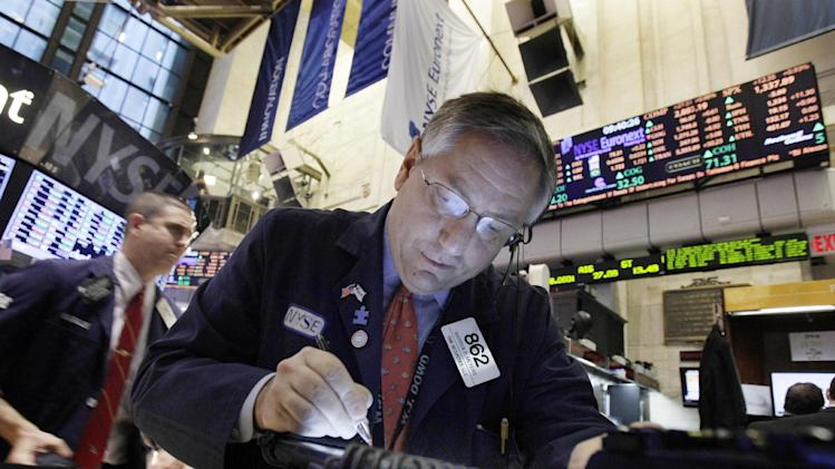 Trader Warren Meyers, right, is illuminated by his handheld device as he works on the floor of the New York Stock Exchange Friday, Feb. 3, 2012. U.S. stocks are opening sharply higher after the unemployment rate dropped to the lowest in two years. (AP Photo/Richard Drew)