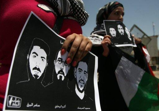 Activists hold pictures of jailed Palestinian prisoners during a demonstration in front of Ofer prison, near Ramallah