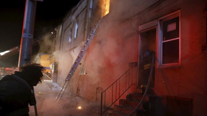 An explosion rocks a building and sends debris flying on Baltimore's East Biddle street as fire fighters attack a fire set by rioters in a convenience store and residence during clashes in Baltimore, Maryland