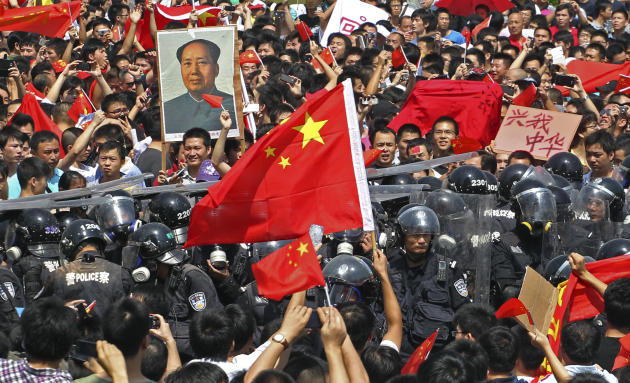 Chinese demonstrators raise national flags as they confront riot policemen during a protest against Japan in Shenzhen, China Sunday, Sept. 16, 2012. Protesters in China began another day of demonstrat