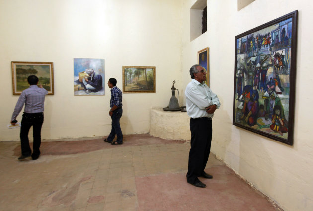 In this Monday, May 7, 2012 photo, visitors look at the paintings during the Babylon Festival of Culture in Hillah, about 60 miles (95 kilometers) south of Baghdad. Poetry has returned to the Triangle