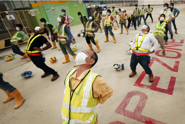 Construction workers wear face masks, to protect them from a heavy smoke haze, as they perform morning exercises in Singapore