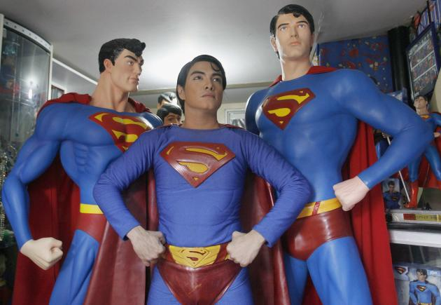 Herbert Chavez poses with his life-sized Superman statues inside his house in Calamba Laguna, south of Manila