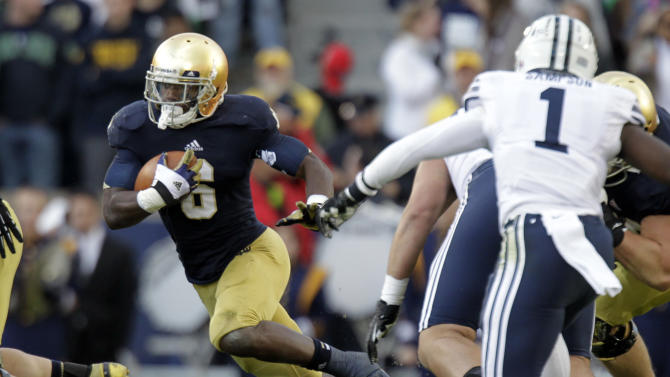 Notre Dame running back Theo Riddick, left, gets past BYU defensive back Joe Sampson to pick up a first down during the second half of an NCAA college football game in South Bend, Ind., Saturday, Oct. 20, 2012. Notre Dame defeated BYU 17-14. (AP Photo/Michael Conroy)