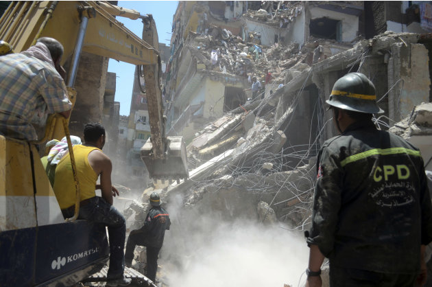 Rescue workers use heavy equipment to remove rubble and look for survivors buried under debris of damaged buildings following the collapse of an 11-story building under construction onto three adjacen