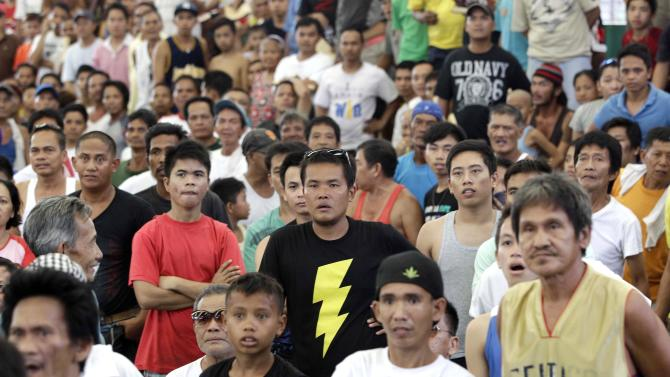 Filipinos look stunned after seeing Filipino boxing hero Manny Pacquiao was knocked out by Mexican Juan Manual Marquez during a live TV broadcast at a multi-purpose hall in suburban Paranaque, south of Manila, Philippines on Sunday, Dec. 9, 2012. Many Filipinos were stunned by Pacquiao's knockout defeat to Marquez, dampening the spirit of a nation battered recently by a powerful typhoon. (AP Photo/Aaron Favila)