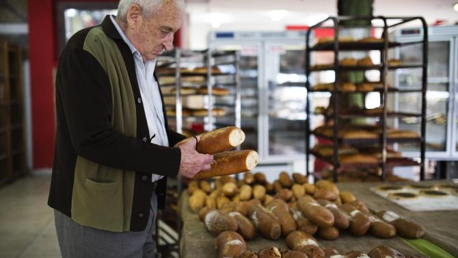 A customer checks loaves of bread at a bakery in the southern Israeli city of Ashkelon