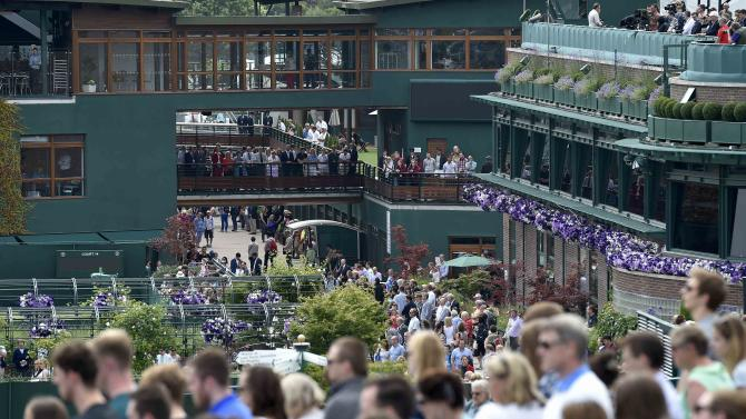 Spectators observe a minutes silence in memory of the 7/7 bombings in London at the Wimbledon Tennis Championships in London