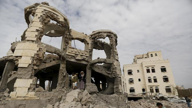 Houthi militants guard the house of Ali Haidar, a Houthi leader, destroyed by a Saudi-led air strike in Sanaa, Yemen