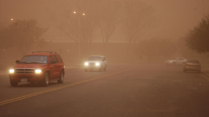 Traffic moves through a dust storm which cast a brown pall over downtown Lubbock, Texas on Monday, Oct. 17, 2011. A strong cold front bringing north and west winds gusting to 60 mph churned up the dust storm that roiled through the Texas South Plains. (AP Photo/The Lubbock Avalanche-Journal, Walt Nett)