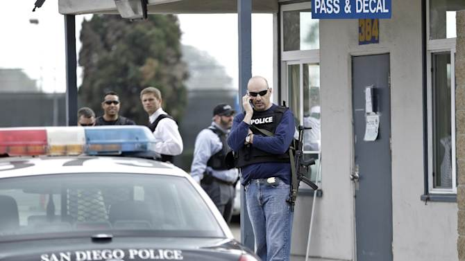 San Diego police officers and federal agents occupy the gate to the Point Loma Naval facility in San Diego Thursday Feb. 7, 2013 during a manhunt for former Los Angeles officer Christopher Dorner in San Diego.  Dorner is suspected of shooting two LAPD officers who were sent to Corona to protect someone Dorner threatened in a rambling online manifesto. Thousands of police officers throughout Southern California and Nevada searched for Dorner, a former Los Angeles officer who was angry over his firing and began a deadly shooting rampage that he warned in an online posting would target those on the force who wronged him. (AP Photo/Lenny  Ignelzi)