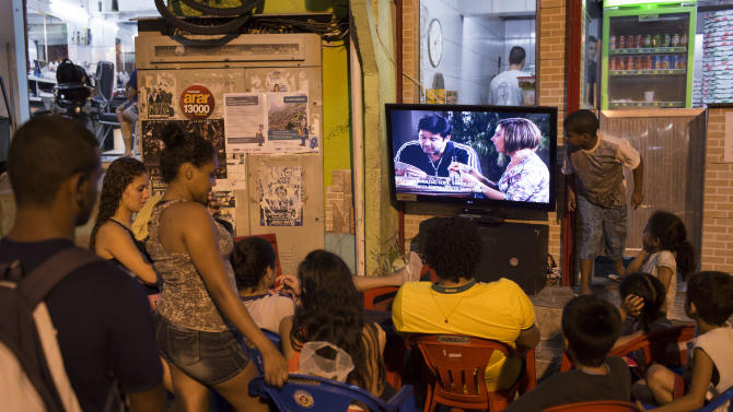 "People watch the final chapter of the soap opera Avenida Brasil in a small outdoor plaza in the Dona Marta slum in Rio de Janeiro, Brazil, Friday, Oct. 19, 2012. ""Telenovelas,"" prime-time soap operas with average runs of 200 episodes, are hugely popular in Brazil, where the plot lines often become front page news and where discussions of the heroes and villains are a major topic of conversation. (AP Photo/Felipe Dana)"