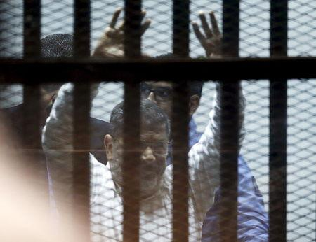 Ousted Egyptian President Mohamed Mursi gestures after his trial behind bars at a court in the outskirts of Cairo
