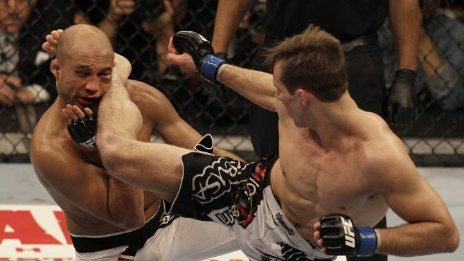 Rory MacDonald, right, kicks BJ Penn in the third round of a welterweight mixed martial arts bout at a UFC on FOX event in Seattle, Saturday, Dec. 8, 2012. MacDonald won by unanimous decision. (AP Photo/Jeff Chiu)