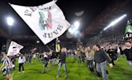 A Juventus supporter waves the club's flag while celebrating at the end of the Serie A football match against Cagliari at Nereo Rocco stadium in Trieste. Juventus won the match 2-0 to win the Italian championship