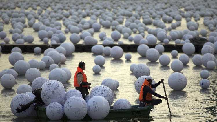 """Workers arrange """"wishing spheres"""" as part of an art installation on the Singapore River"""