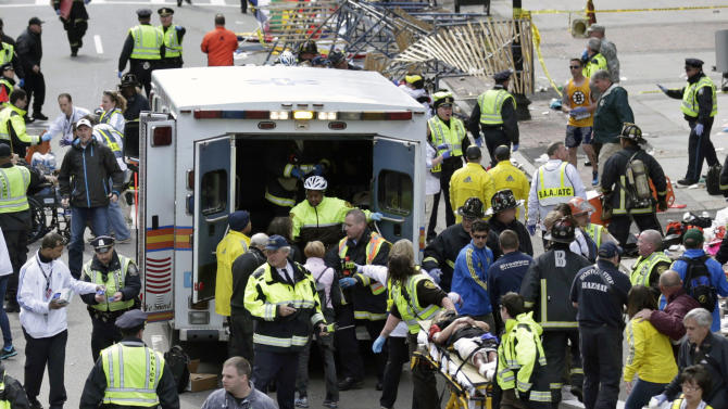 FILE - Medical workers aid injured people at the finish line of the 2013 Boston Marathon following an explosion in Boston, Monday, April 15, 2013. More than 200 were injured in the bombings and no one knows yet what the total medical costs will be. (AP Photo/Charles Krupa)