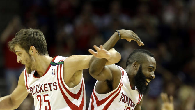 Houston Rockets' Chandler Parsons (25) and James Harden (13) celebrate during a timeout after teammate Toney Douglas hit a three-point shot during the fourth quarter of an NBA basketball game against the Boston Celtics Friday, Dec. 14, 2012, in Houston. The Rockets beat the Celtics 101-89. (AP Photo/David J. Phillip)