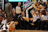 San Antonio Spurs' Tony Parker (R) jump over Utah Jazz's Devin Harris during game four of their NBA Western Conference series on May 7. The Spurs swept Utah out of the NBA playoffs with a 87-81 victory