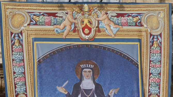 "The tapestry of  St. Hildegard of Bingen hangs from the facade of St. Peter's Basilica during the opening of the synod of bishops in St. Peter's Square, at the Vatican, Sunday, Oct. 7, 2012. Pope Benedict XVI has named two new ""doctors"" of the church, conferring the Catholic Church's highest honor on a 16th-century Spanish preacher St. John of Avila, and  to St. Hildegard of Bingen, and a 12th— century German mystic who wasn't even officially recognized as a saint until earlier this year. (AP Photo/Alessandra Tarantino)"