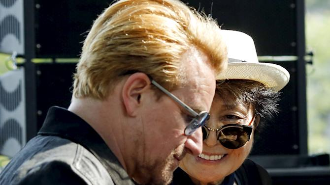 Artist Yoko Ono, the widow of John Lennon, speaks to Irish singer Bono after her remarks during the unveiling of a tapestry honoring Lennon at Ellis Island in New York