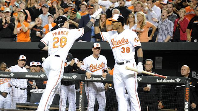 Jimmy Paredes of the Baltimore Orioles congratulates Steve Pearce (L) on his three-run home during the game against the Toronto Blue Jays in Baltimore on September 16, 2014