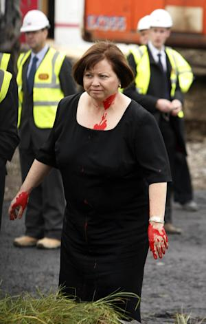 Ireland's Health Minister Mary Harney is seen after she was pelted with a paint-filled balloon during the opening of a new mental health facility in west Dublin, Monday, Nov. 1, 2010. Ireland's health minister has been pelted with red paint as tempers grow over government plans to slash euro1 billion (US$1.4 billion) from the costs of running an overloaded hospital network. (AP Photo/Niall Carson, PA) ** UNITED KINGDOM OUT  **