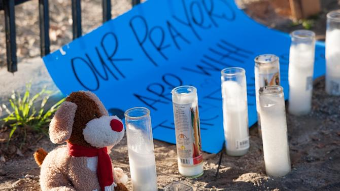 A stuffed animal, candles and a sign are part of a makeshift memorial near the Inland Regional Center on December 5, 2015, in San Bernardino, California