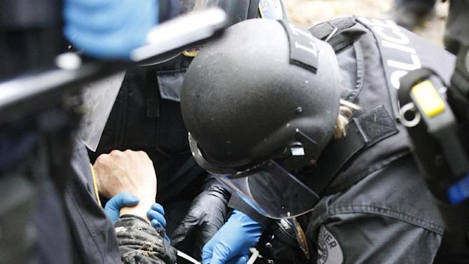 """Police officers arrest a protester in the Portland encampment Sunday, Nov. 13, 2011, in, Portland, Ore. In a tense escalation of the Occupy Portland protest, police in riot gear Sunday surrounded demonstrators in a downtown park area after hundreds of people defied the mayor's order to leave the park by midnight. By early afternoon, officers had mostly surrounded the camp where the protesters were holding a """"general assembly"""" meeting to discuss their next moves following the eviction order. (AP Photo/Rick Bowmer)"""