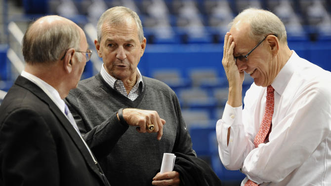 Former Connecticut head coach Jim Calhoun, center, speaks with Associated Press writer Jim O'Connell, left, as Syracuse head coach Jim Boeheim, right, reacts, before an NCAA college basketball game between the two teams in Hartford, Conn., Wednesday, Feb. 13, 2013. (AP Photo/Jessica Hill)