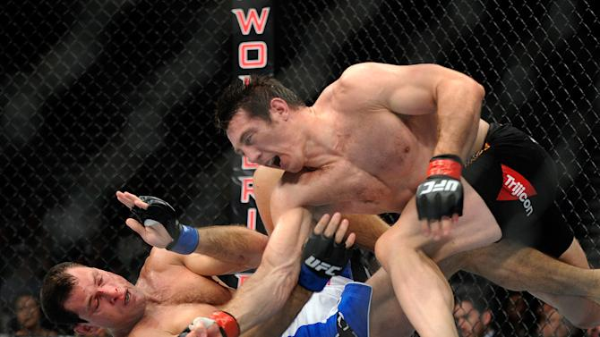 Tim Kennedy punches Roger Gracie during their UFC 162 mixed martial arts middleweight bout at the MGM Grand Garden Arena on Saturday, July 6, 2013, in Las Vegas. kennedy won the fight by an unanimous decision after three rounds. (AP Photo/David Becker)