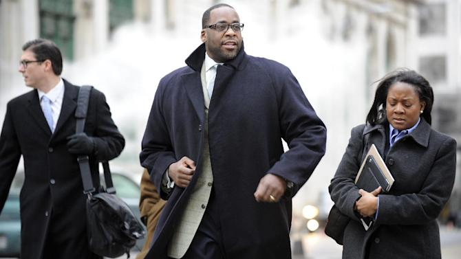 Kwame Kilpatrick, center, heads to federal court in Detroit on Monday Monday Jan. 7, 2013.  Derick Miller, a longtime confidant of the former Detroit mayor, testified against Kilpatrick at his corruption trial Monday telling jurors he passed thousands of dollars to Kilpatrick from a contractor at the city's convention center. Kilpatrick resigned as mayor in 2008. Miller pleaded guilty to corruption in 2011 and agreed to cooperate with prosecutors. (AP Photo/Detroit News,David Coates )  DETROIT FREE PRESS OUT; HUFFINGTON POST OUT