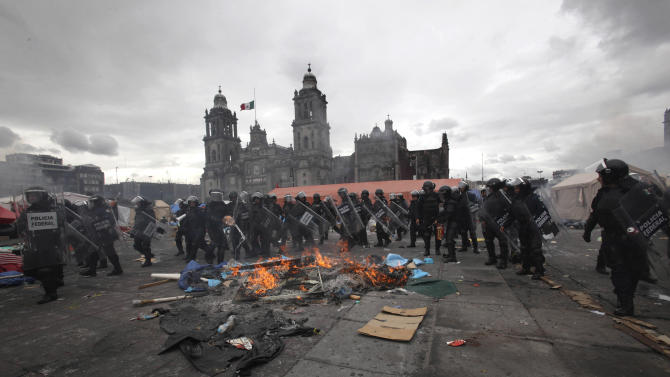 Police enter the Zocalo, or main plaza, in a mass eviction operation of striking teachers, Friday, Sept. 13, 2013. Minutes after a late-afternoon government deadline for teachers to leave from the city's main plaza, where they have camped out for weeks, riot police moved in, firing tear gas and ducking hurled rocks in a confrontation culminating weeks of protests against an education reform. (AP Photo/Marco Ugarte)