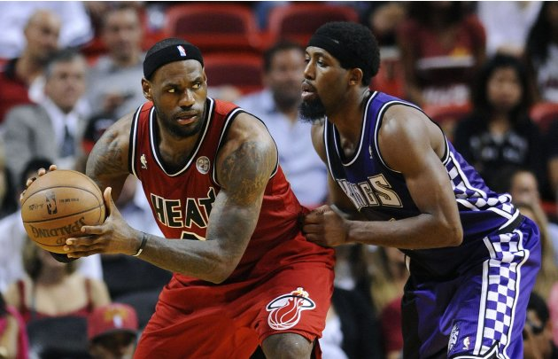 Miami Heat's James is defended by Sacramento Kings' Salmons during overtime of their NBA basketball game in Miami