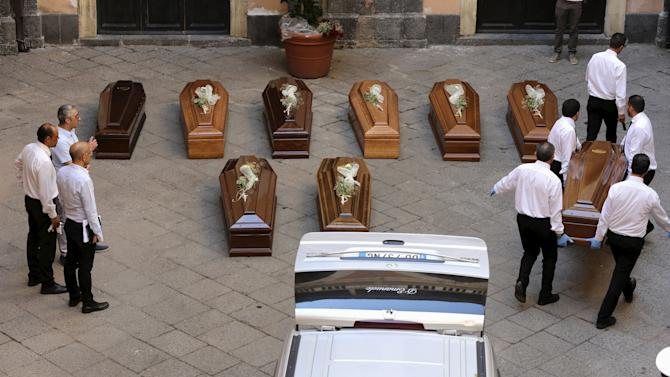 Pallbearers prepare the coffins of 13 unidentified migrants who died in the April 19, 2015 shipwreck, at an inter-faith funeral service in Catania