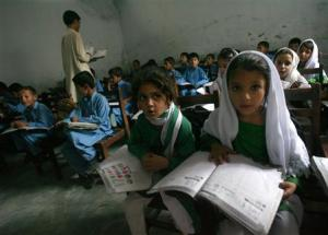 Female students Shaista (R), 12, and Rabia (L), 10, read aloud while taking part in class in Buner district