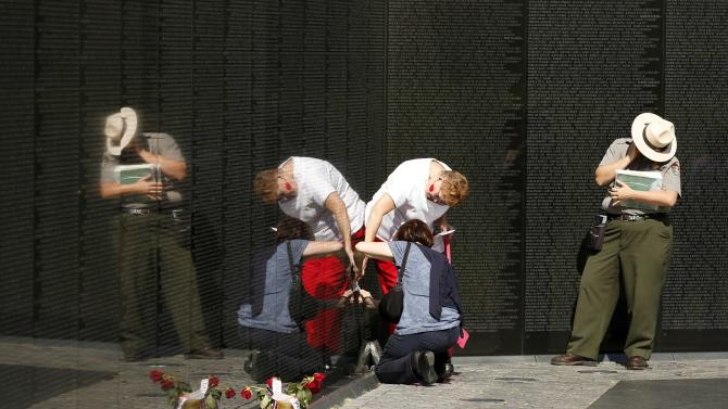 A U.S. National Park Ranger is reflected on a wall while assisting visitors with name rubbing at the Vietnam Veterans Memorial in Washington