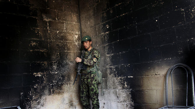 An Afghan army soldier stands guard in the destroyed courthouse in Farah, western Afghanistan, Thursday, April 4, 2013. Suicide bombers disguised as Afghan soldiers stormed a courthouse Wednesday in a failed bid to free more than a dozen Taliban prisoners in western Afghanistan, officials said. Tens of people, including the nine attackers were reported killed in the fighting. The assault in Farah province was the latest example of the Taliban's ability to strike official institutions despite tight security measures. (AP Photo/Hoshang Hashimi)